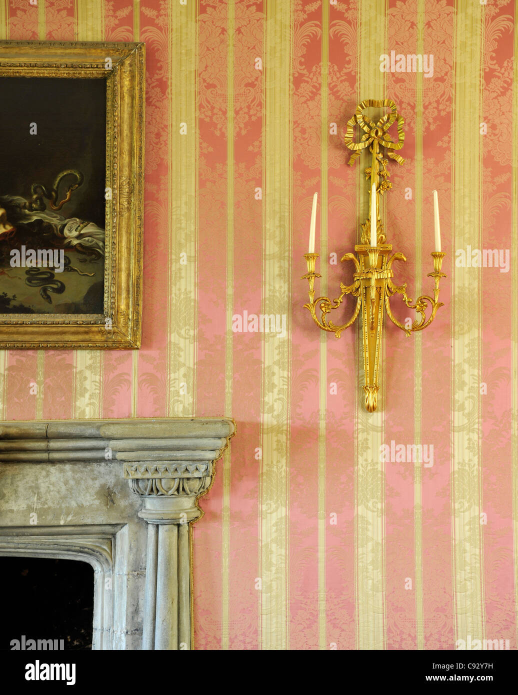 Candle sconces were used in historic country houses as wall lighting for dark rooms. Flintshire, Wales. - Stock Image
