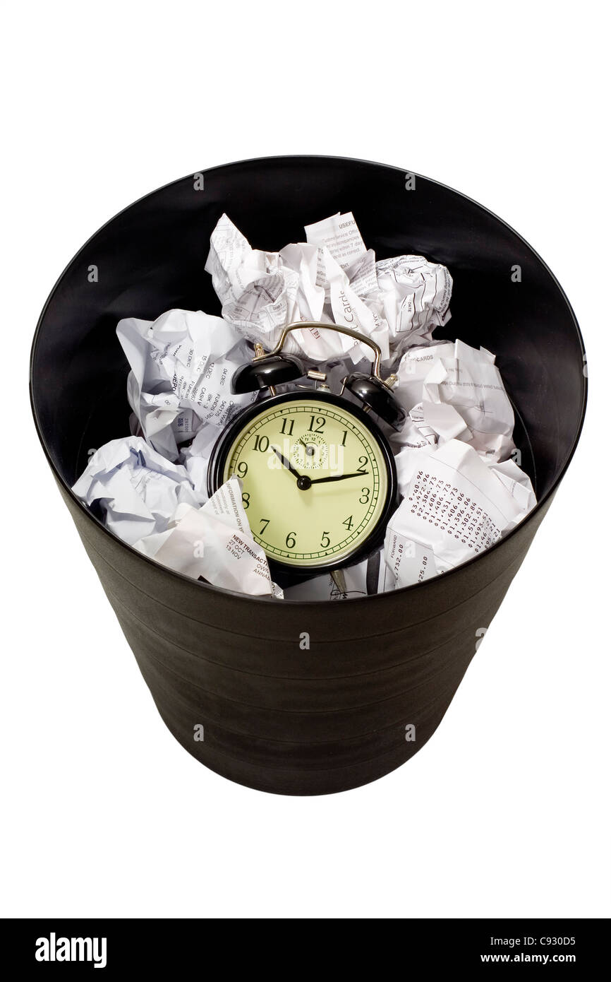 Clock in waste paper basket isolated on white background - Stock Image