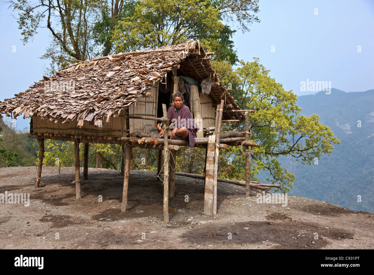 A man sits on the veranda of his small house, raised on stilts, situated precariously on the edge of a steep drop - Stock Image