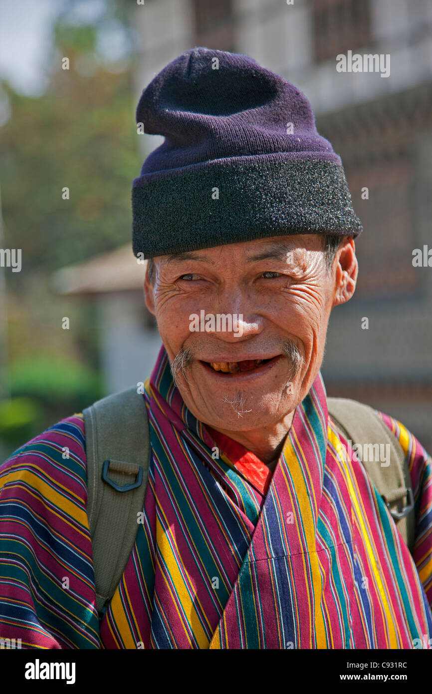 An old man at Trashigang wearing the traditional gho robe of all Bhutanese men. - Stock Image