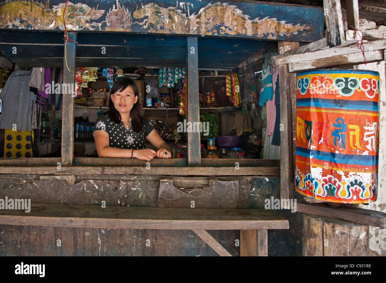A woman shopkeeper in her small rural shop on the banks of the Kolounchu River just outside Trashigang. - Stock Image