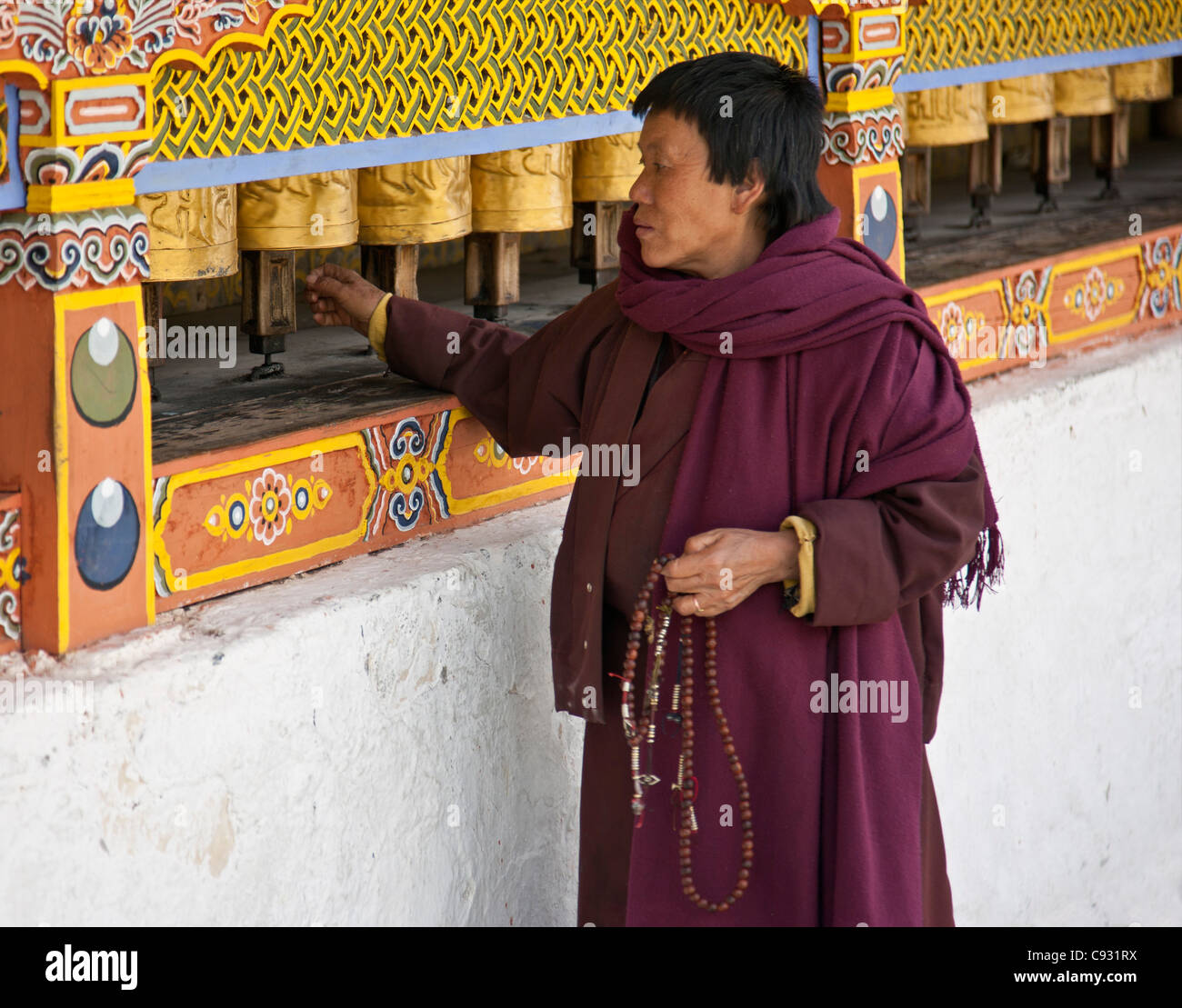 A woman, prayer beads in hand, spins brass prayer wheels at the 18th century Chorten Kora in Trashi Yangtze. - Stock Image