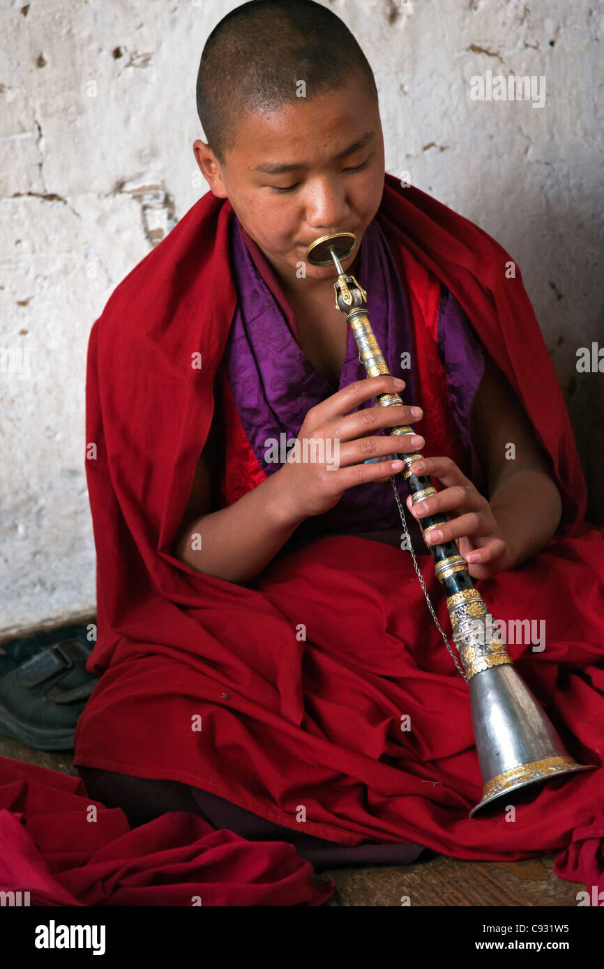 A novice monk plays the lingm, an indigenous Bhutanese flute, at the Dzong, or fortress, at Trashigang. - Stock Image