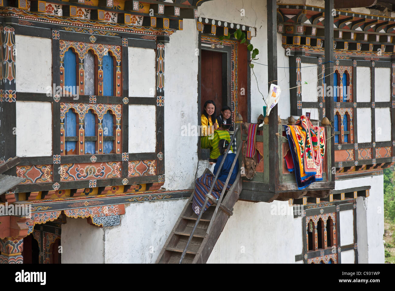 A family eats their mid-day meal on the porch of their traditional home outside Mongar. - Stock Image