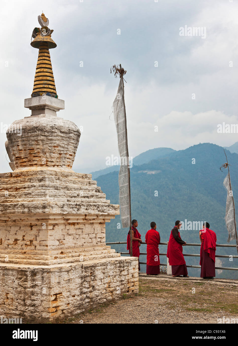 Red-robed monks relax beside a chorten or stupa near Mongar. - Stock Image