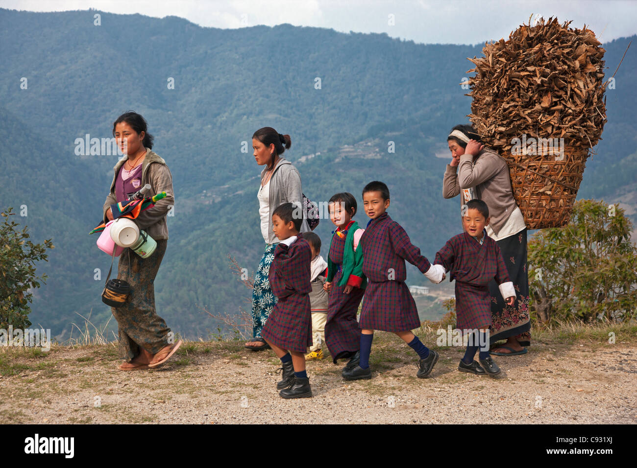 Mothers return home with their schoolchildren near Mongar. - Stock Image