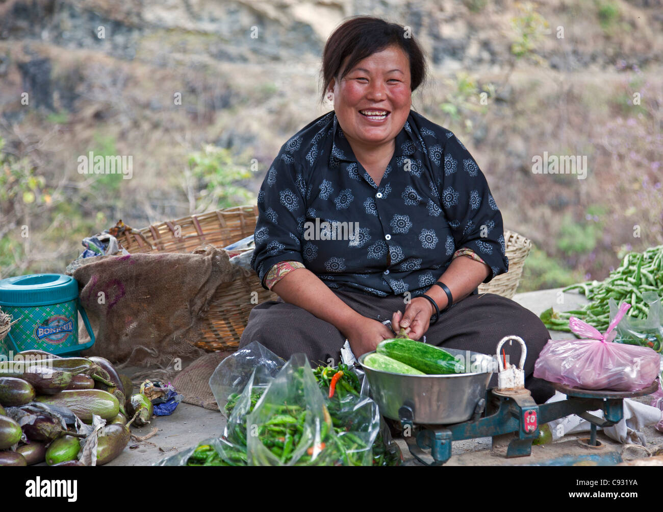 A woman sells vegetables at a roadside stall outside Mongar in East Bhutan. - Stock Image