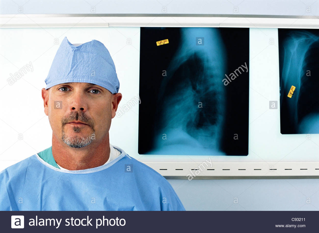 Portrait of serious surgeon in front of x-rays - Stock Image