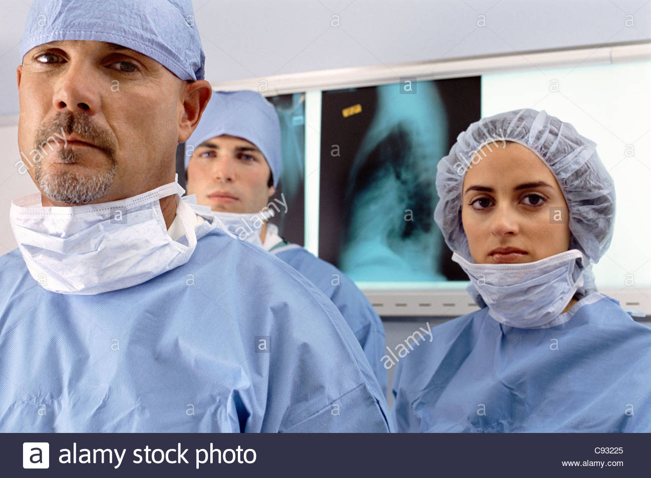 Portrait of serious surgeons in front of x-rays - Stock Image