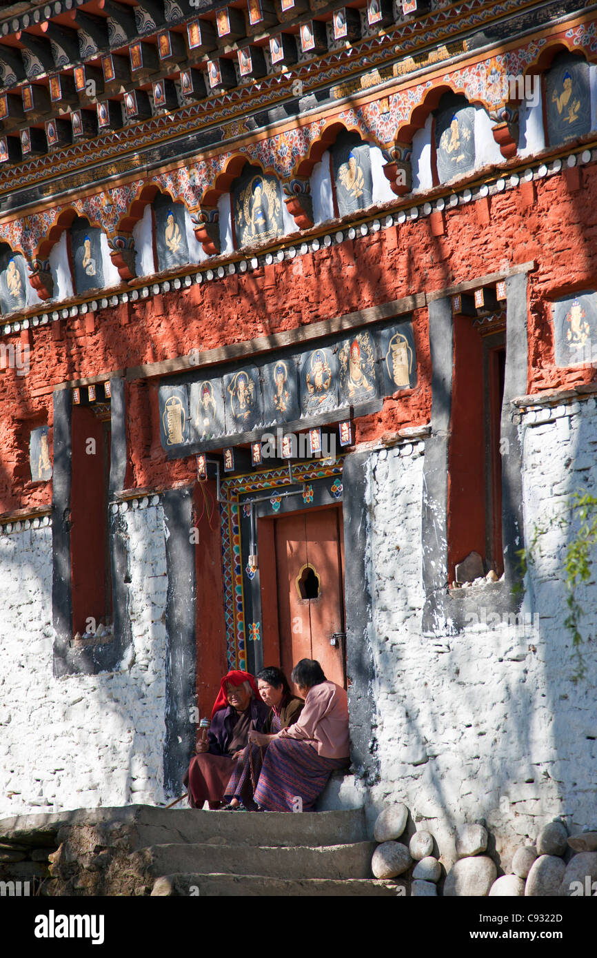 Three women gossip on the steps of a finely decorated building housing a prayer wheel rotated by a fast running - Stock Image