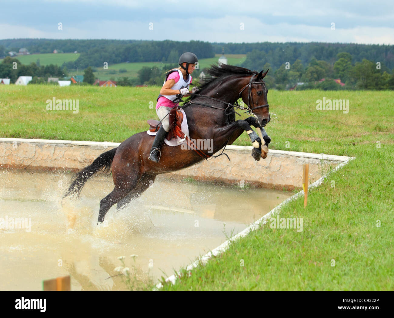 Horse rider jumps a water during a three day eventing - Stock Image