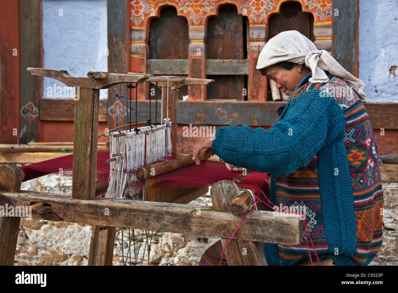 A woman weaving cloth outside her house on the outskirts of Zugney village which is renown for its weaving. - Stock Image