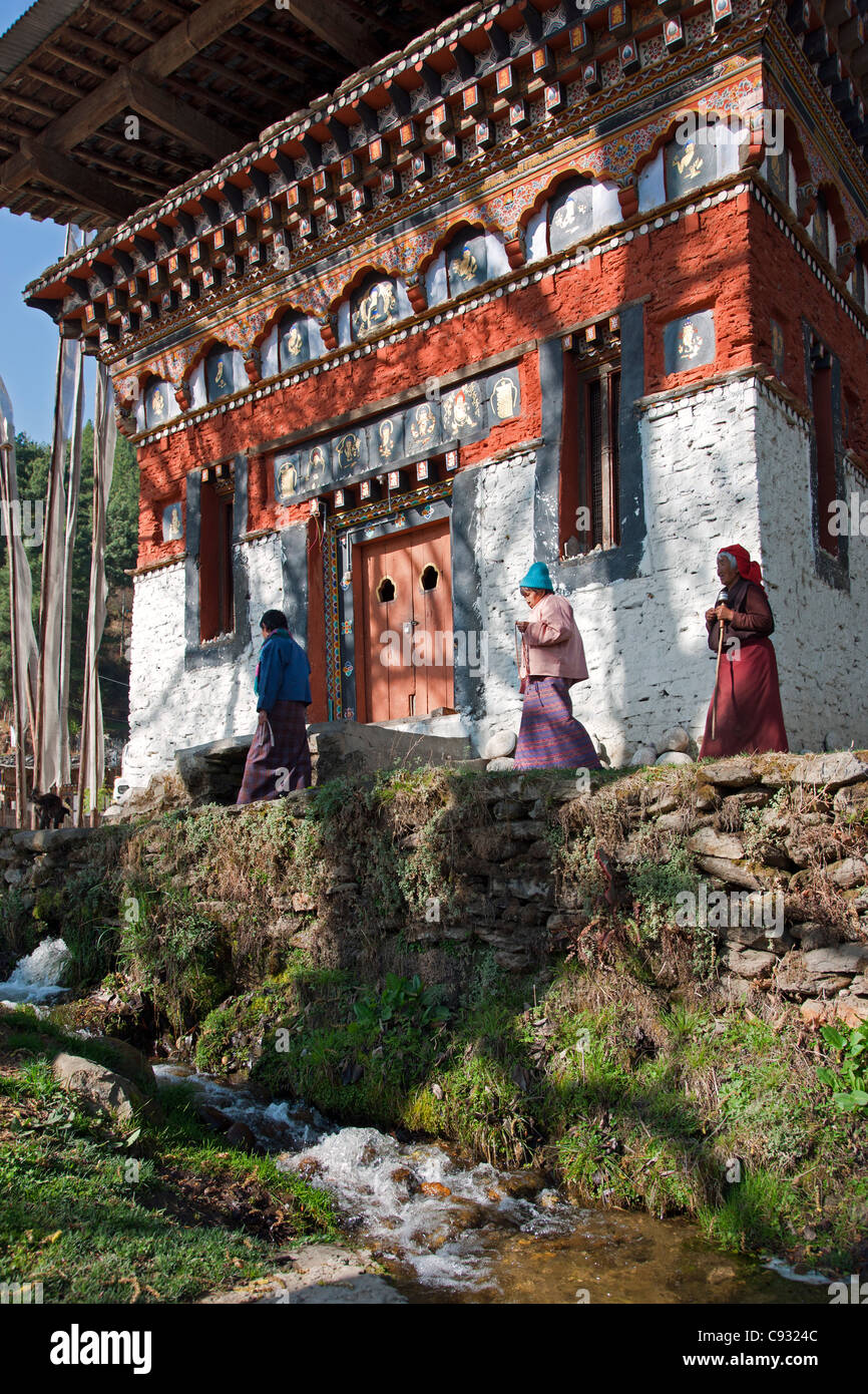Three women walk in a clockwise direction round a finely decorated building housing a prayer wheel. - Stock Image