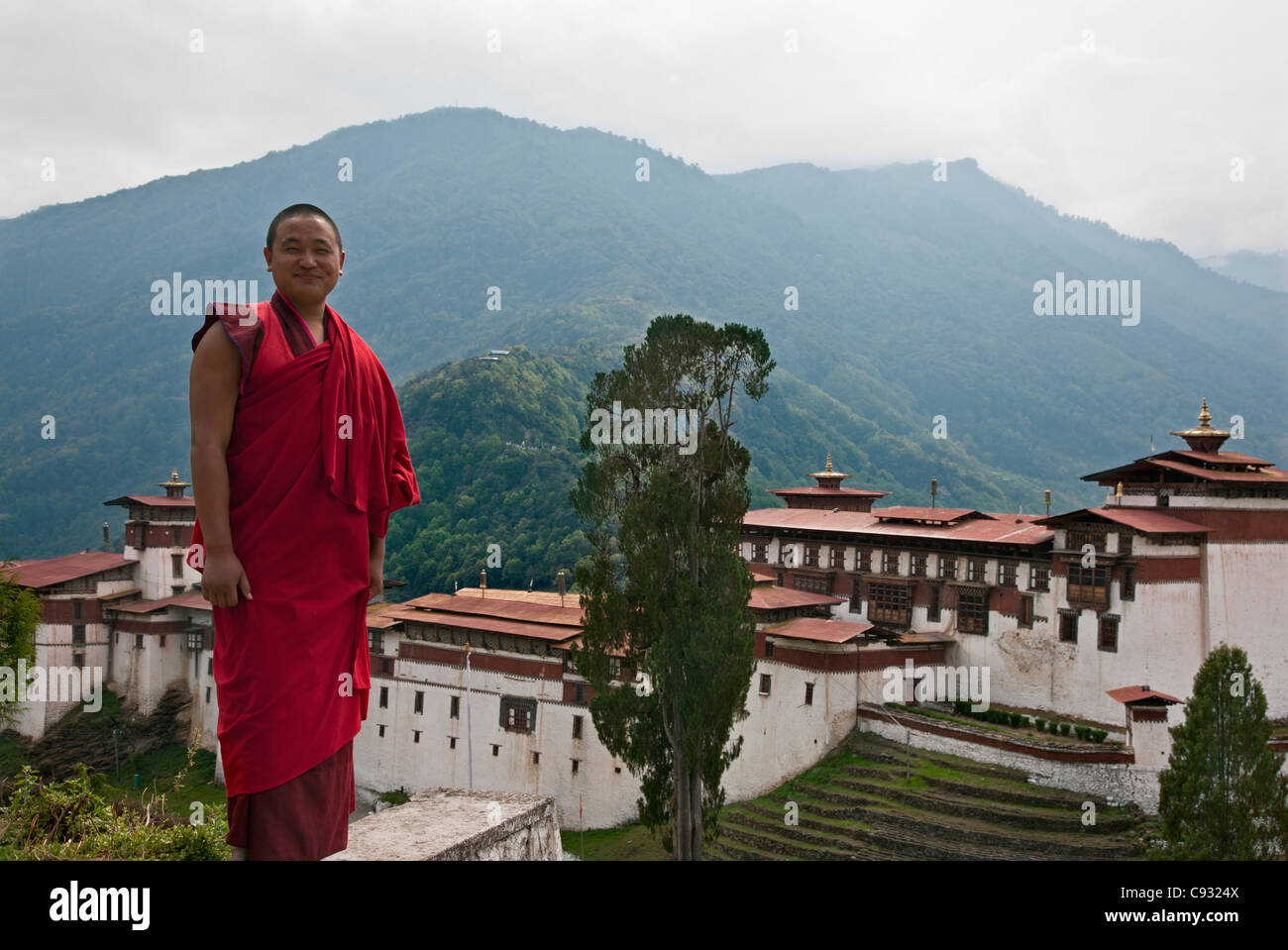 A beaming monk stands in front of Trongsa Dzong which was built in the 1640s. - Stock Image
