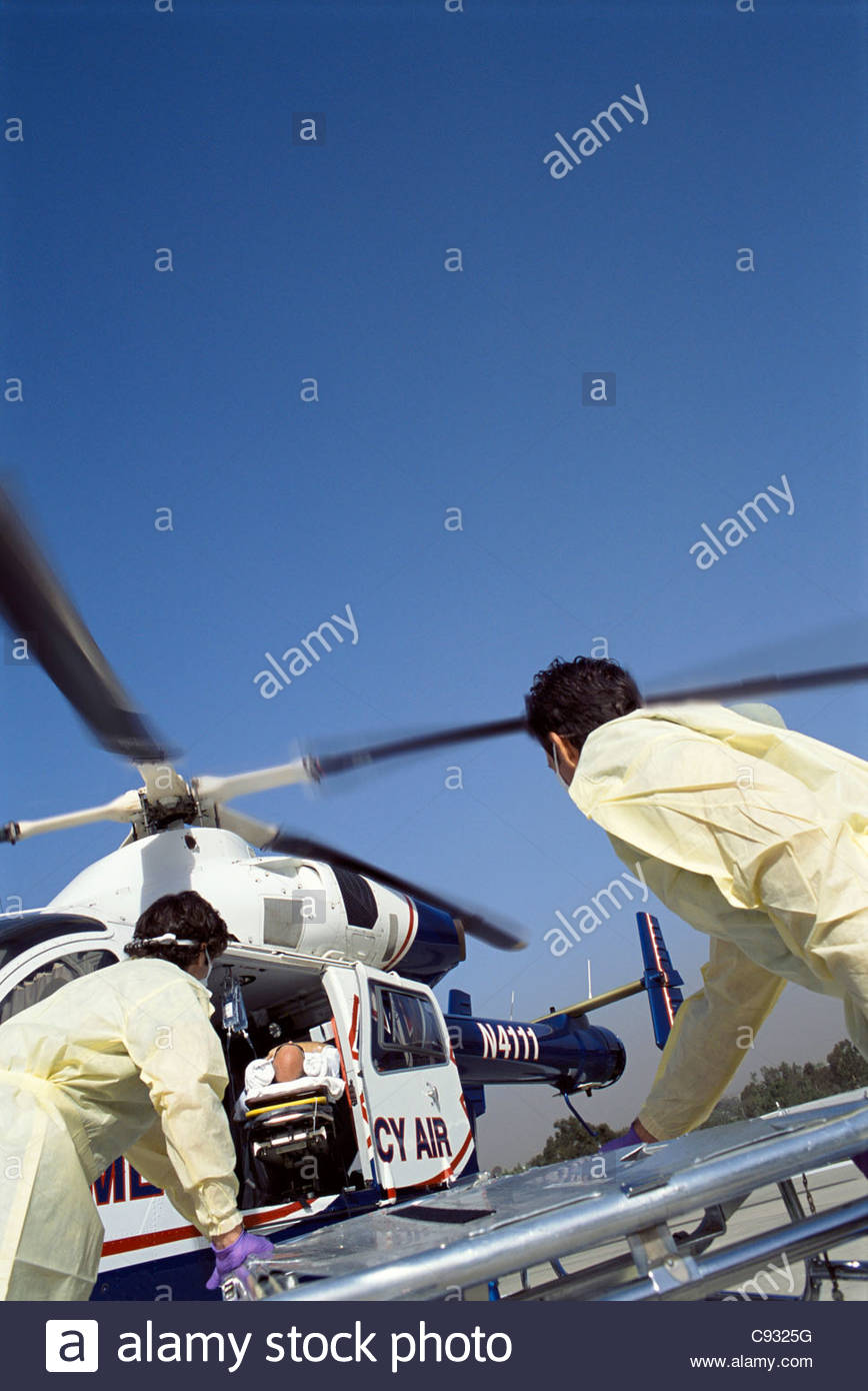 Paramedics rushing patient on gurney to emergency airlift helicopter - Stock Image