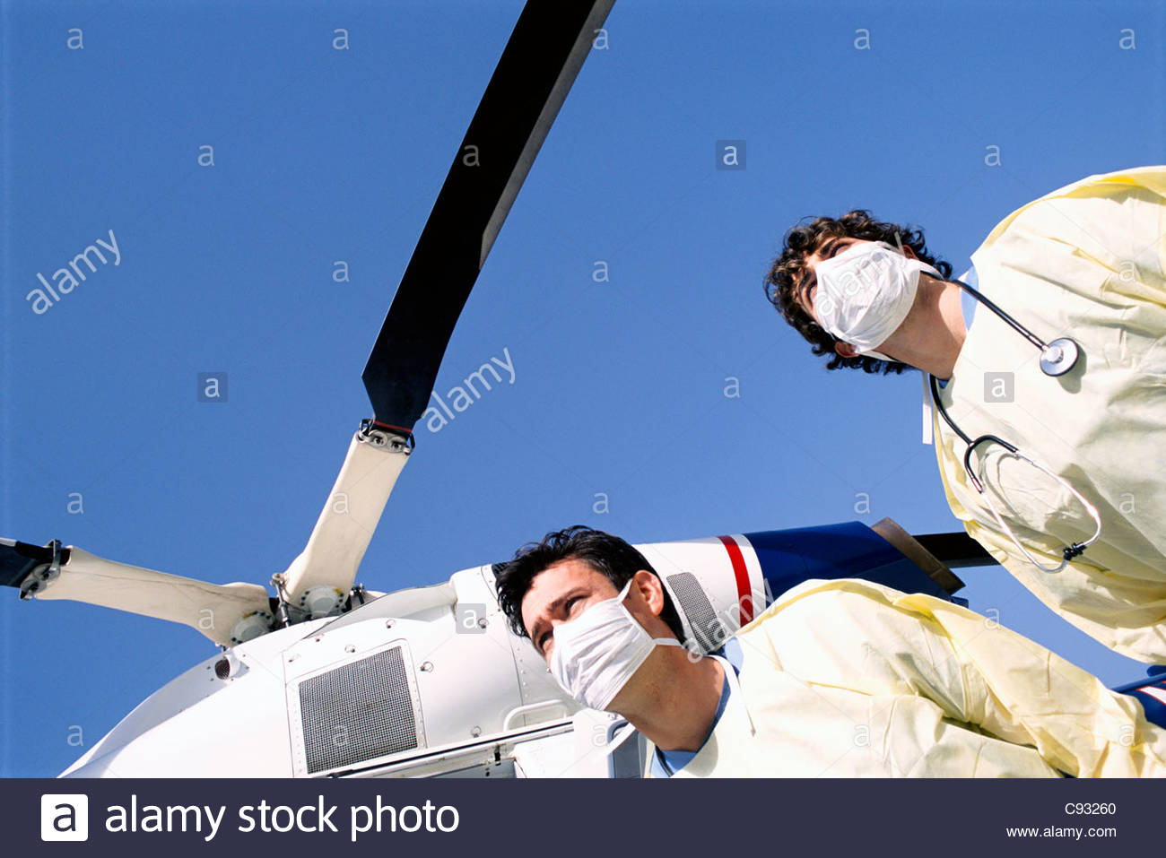 Doctors with surgical masks standing below emergency airlift helicopter - Stock Image