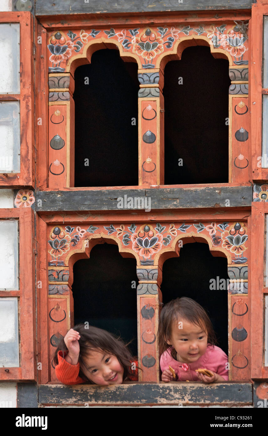 Children look out of a house with traditional Bhutanese decorated windows at Trongsa. - Stock Image