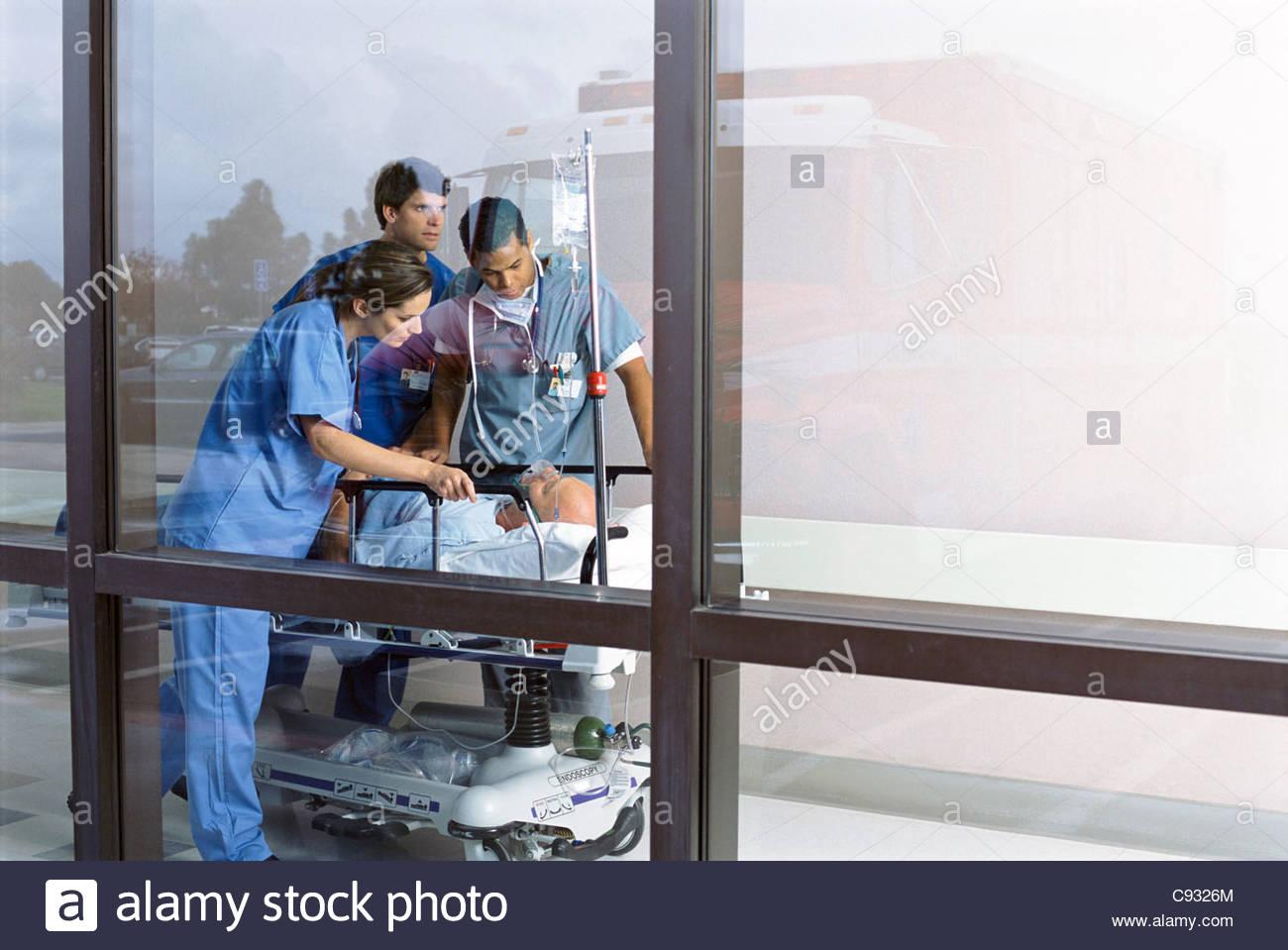 Doctors in corridor tending to patient on hospital gurney - Stock Image