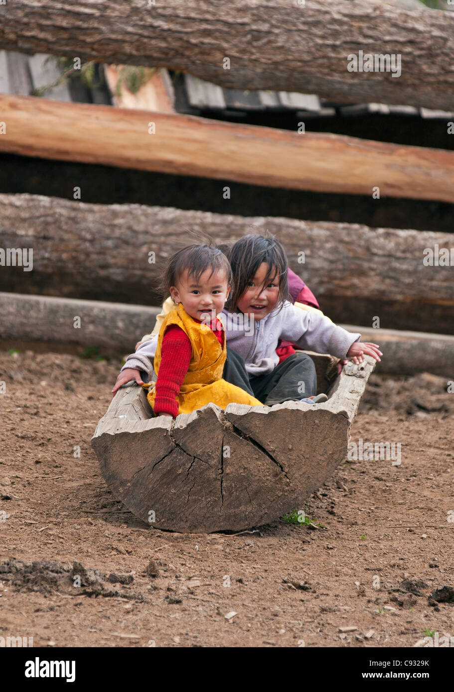 Young children play in an animal feed trough on their parents   farm in the beautiful Phobjikha Valley. - Stock Image
