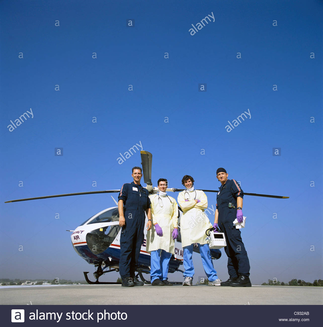 Portrait of doctors and paramedics outside emergency airlift helicopter - Stock Image