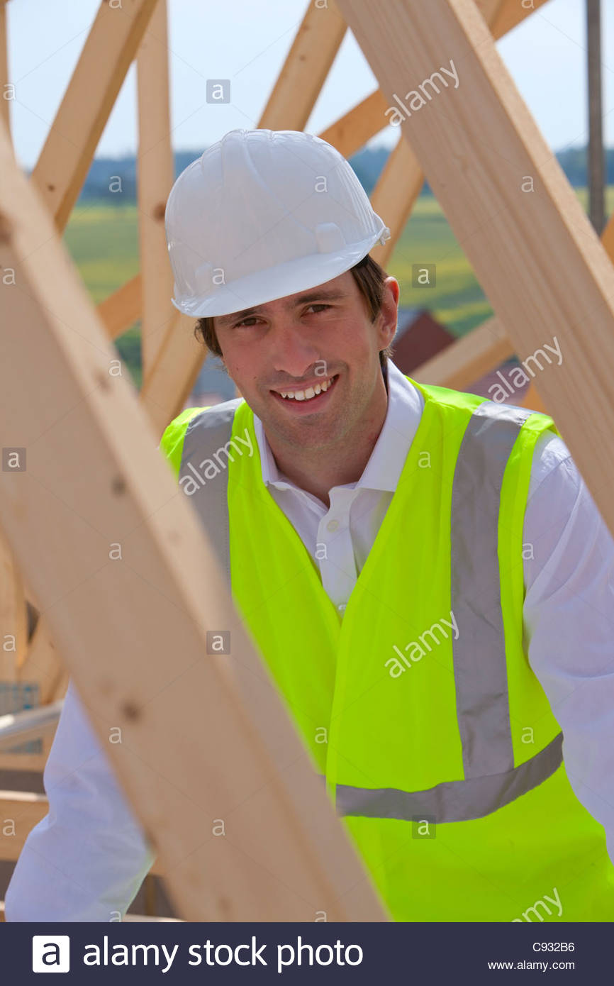 Portrait of smiling construction worker at construction site - Stock Image