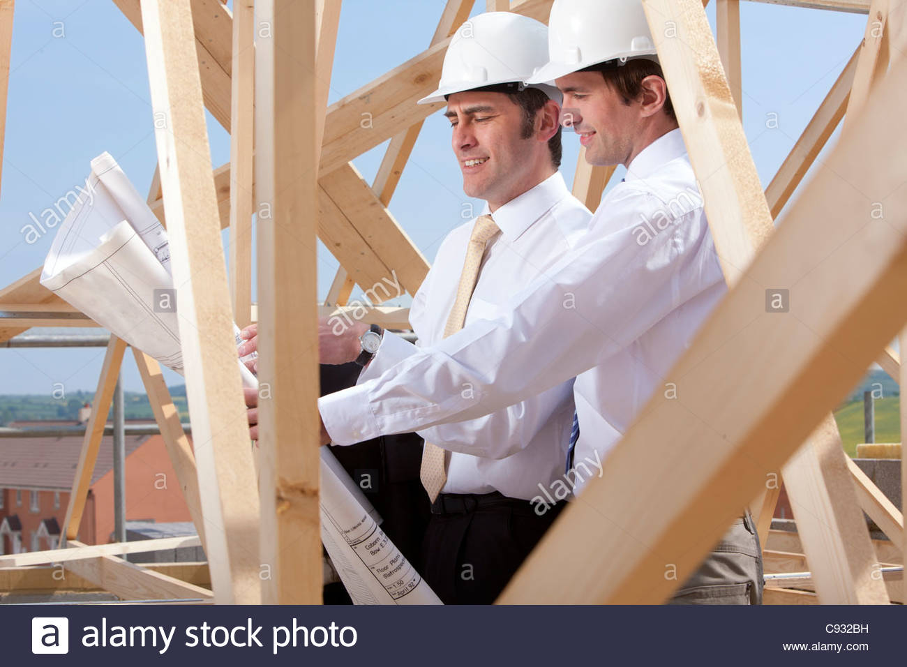 Architects reviewing blueprints at construction site - Stock Image