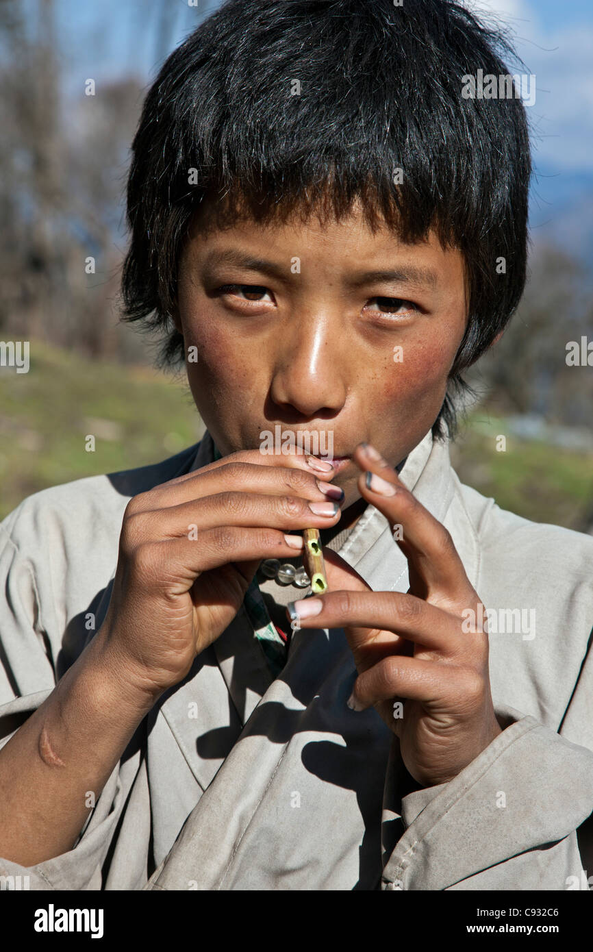 A young lad plays his homemade flute while on the Black Mountains pass known as Lawa La. - Stock Image