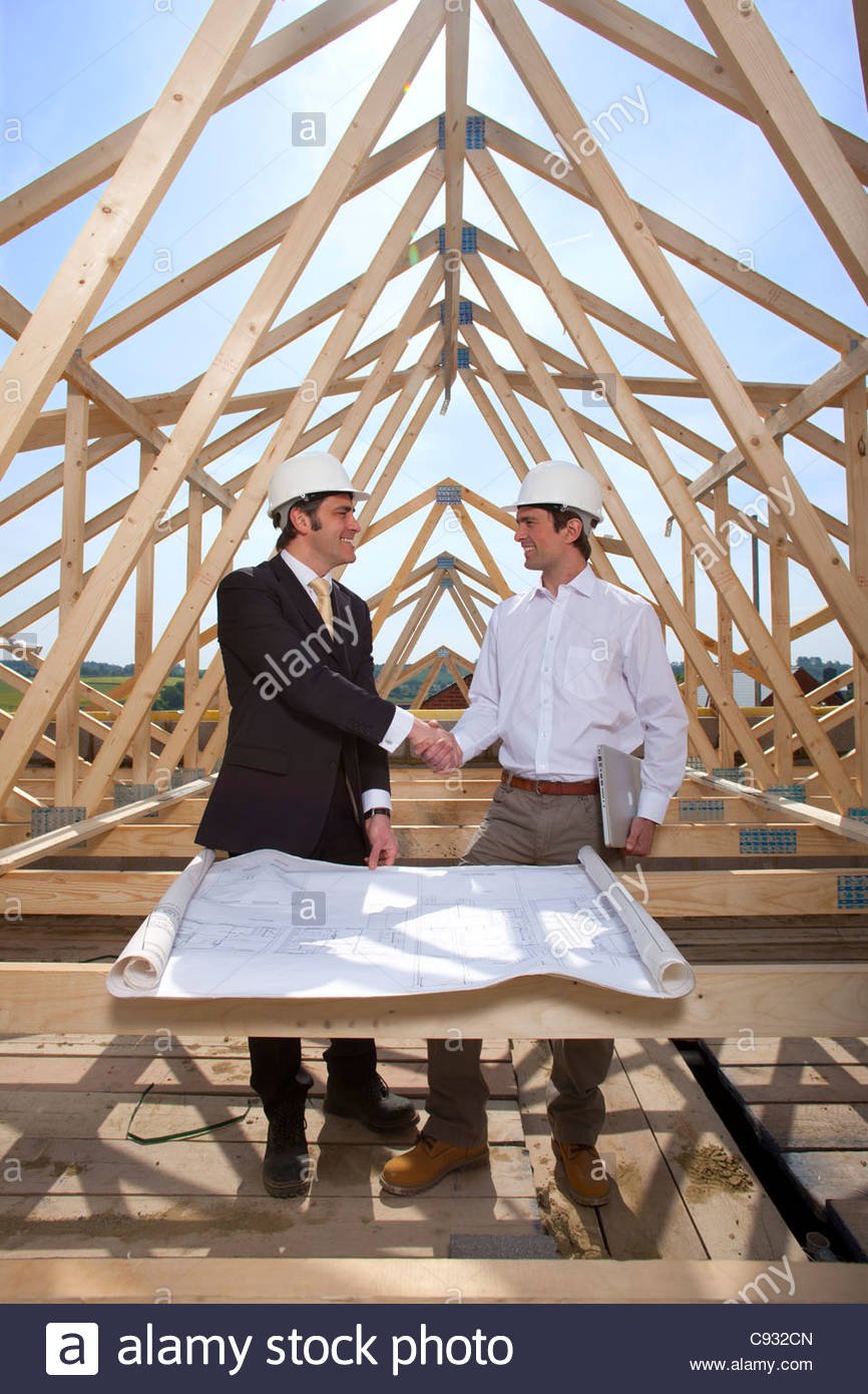 Architects with blueprints handshaking at construction site - Stock Image