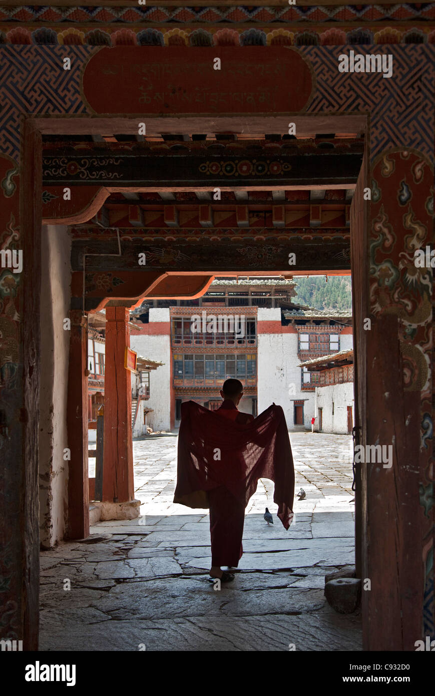 A monk adjusts his red robes as he enters the main courtyard of Wangdue Phodrang Dzong (fortress). - Stock Image