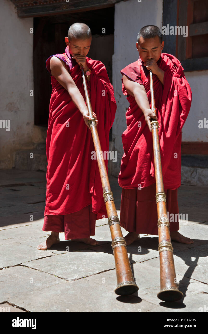 Two monks blow long horns, called dung-chen, in Wangdue Phodrang Dzong (fortress). - Stock Image