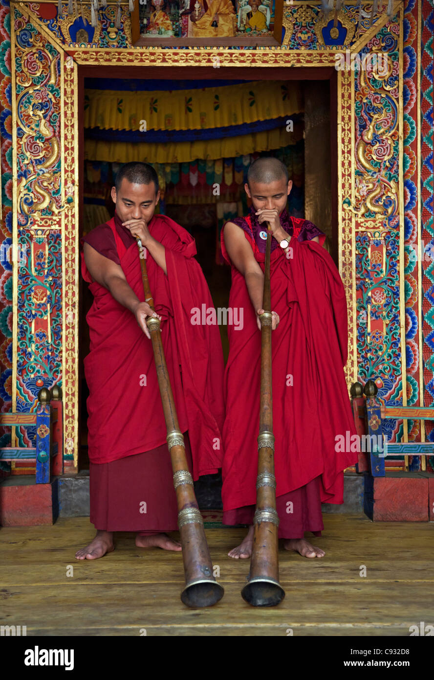 Two monks blow long horns called dung-chen, at the temple of Wangdue Phodrang Dzong (fortress). - Stock Image