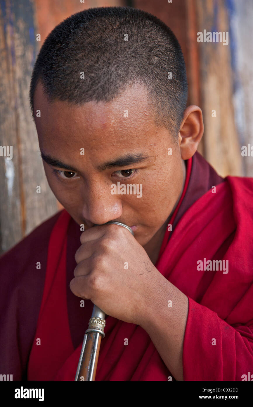 A monk blowing a long horn called dung-chen, at Wangdue Phodrang Dzong (fortress). - Stock Image
