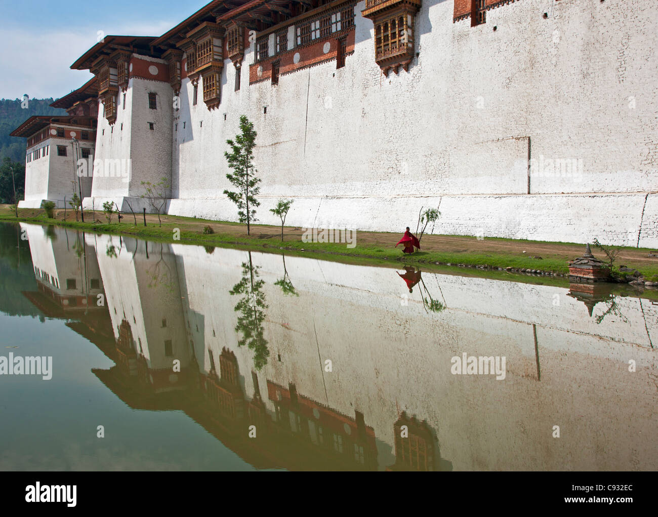 A young monk walks along the outside wall of Punakha Dzong, is the second oldest and largest dzong in Bhutan. - Stock Image