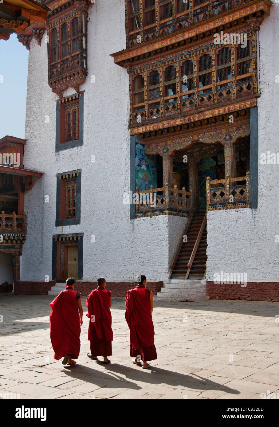 Three monks cross a courtyard in the Punakha Dzong, is the second oldest and largest dzong in Bhutan. - Stock Image