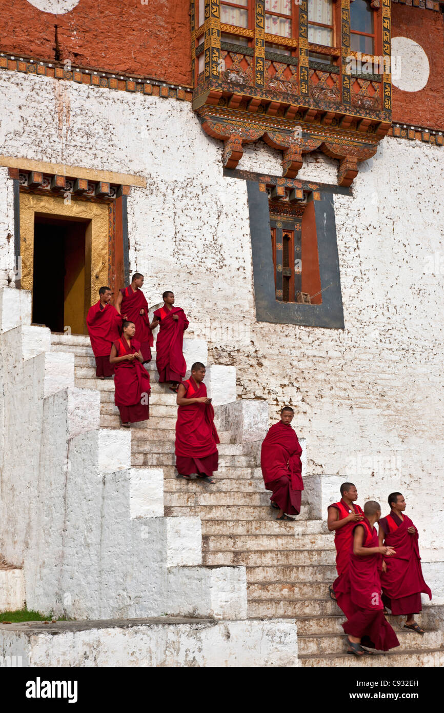 Red robed monks leave the massive Punakha Dzong,  is the second oldest and largest dzong in Bhutan. - Stock Image