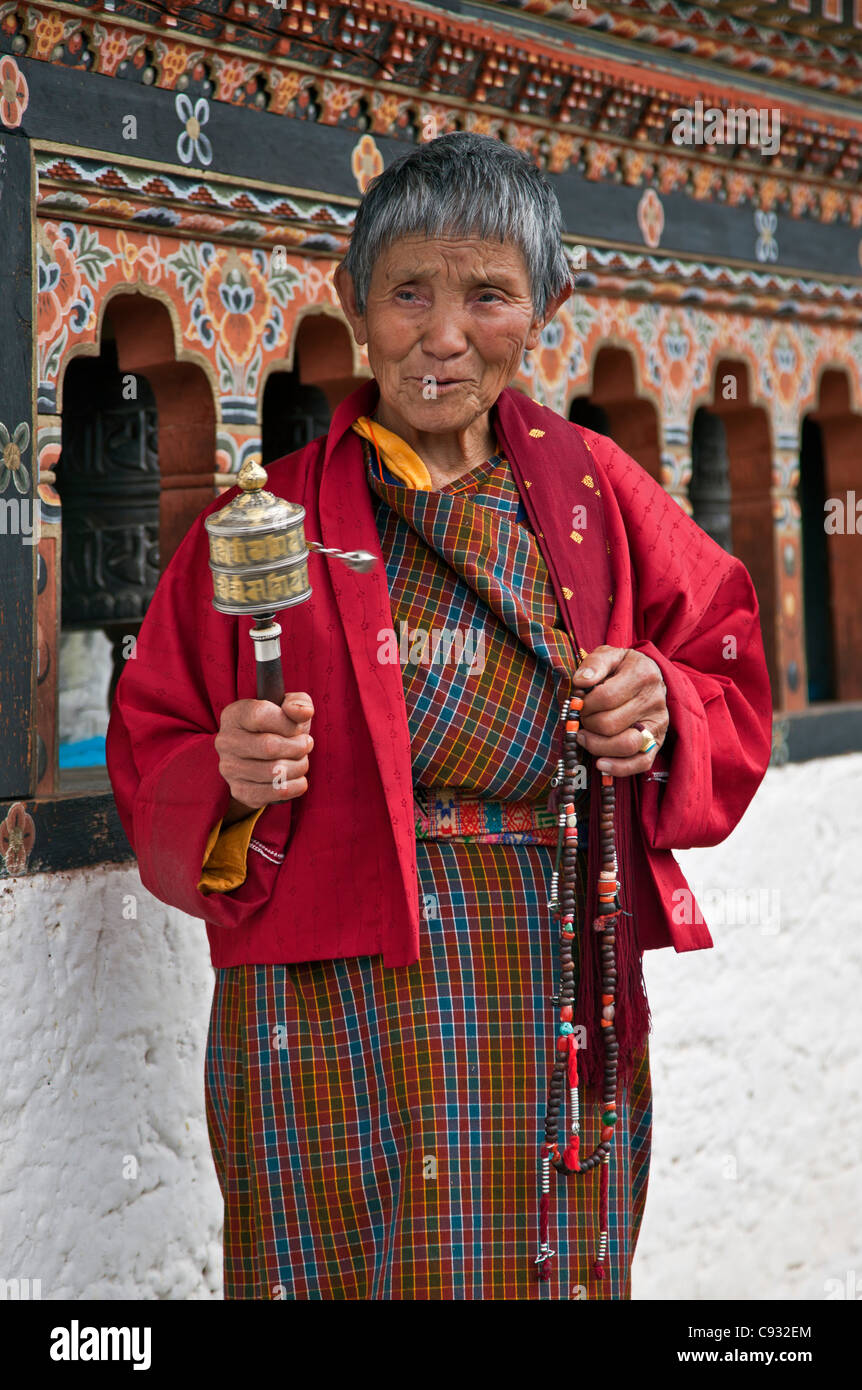A devout Buddhist woman spins her hand-held prayer wheel at Punakha Dzong, is the second oldest and largest dzong - Stock Image