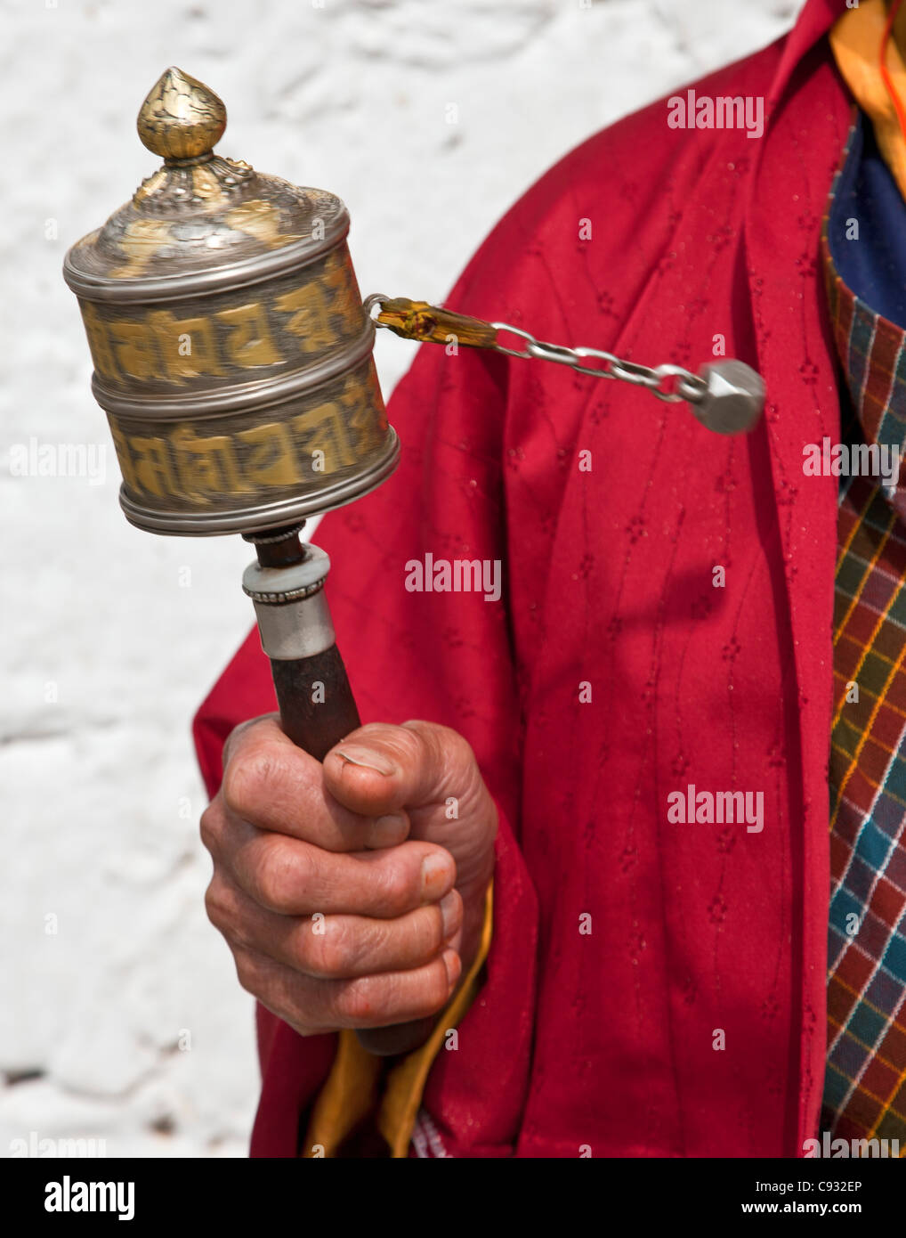 A Buddhist woman spins her hand-held prayer wheel in a clockwise direction. - Stock Image