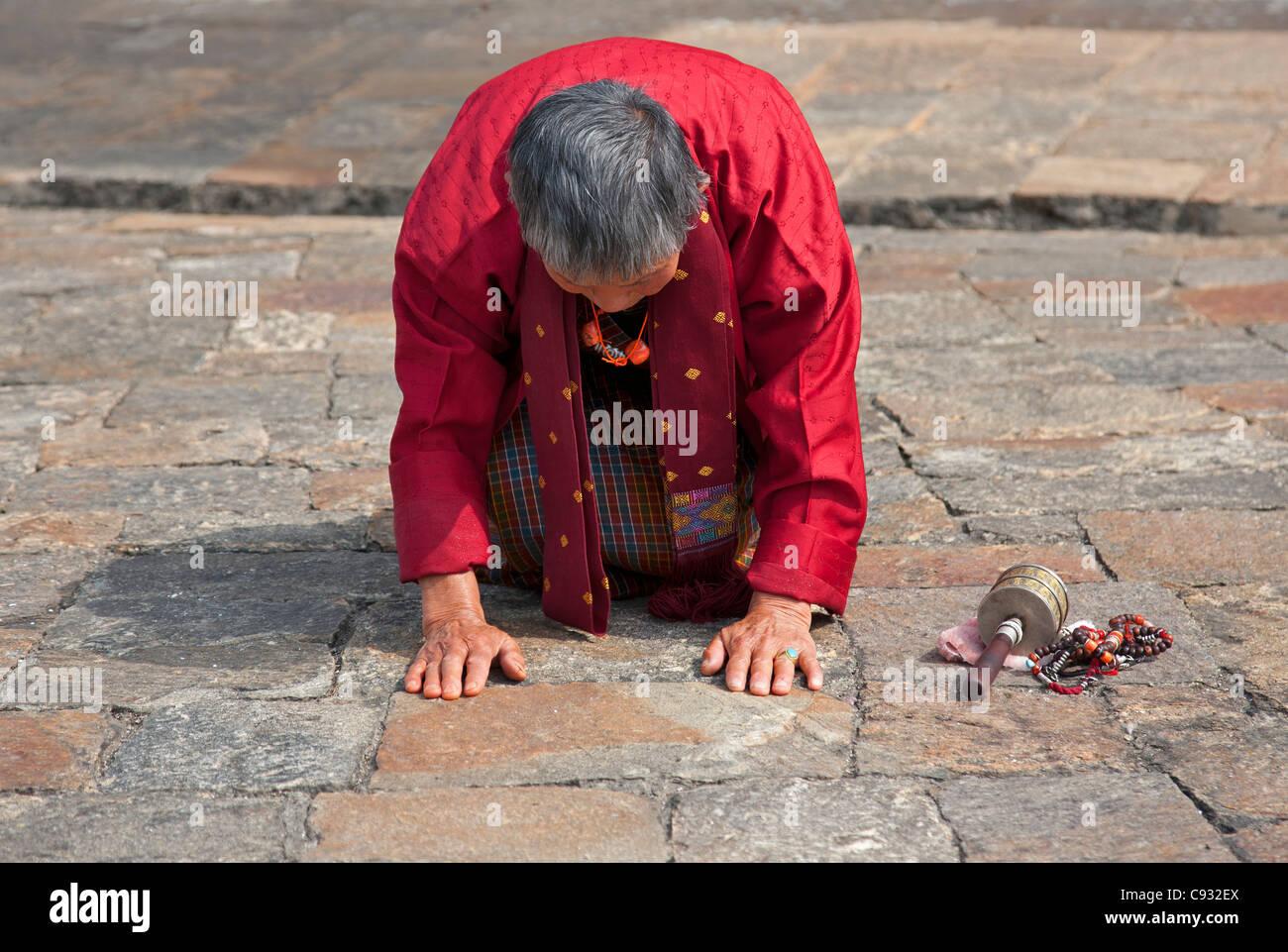 A devout Buddhist woman prays at the 17th century Punakha Dzong, Bhutan. - Stock Image