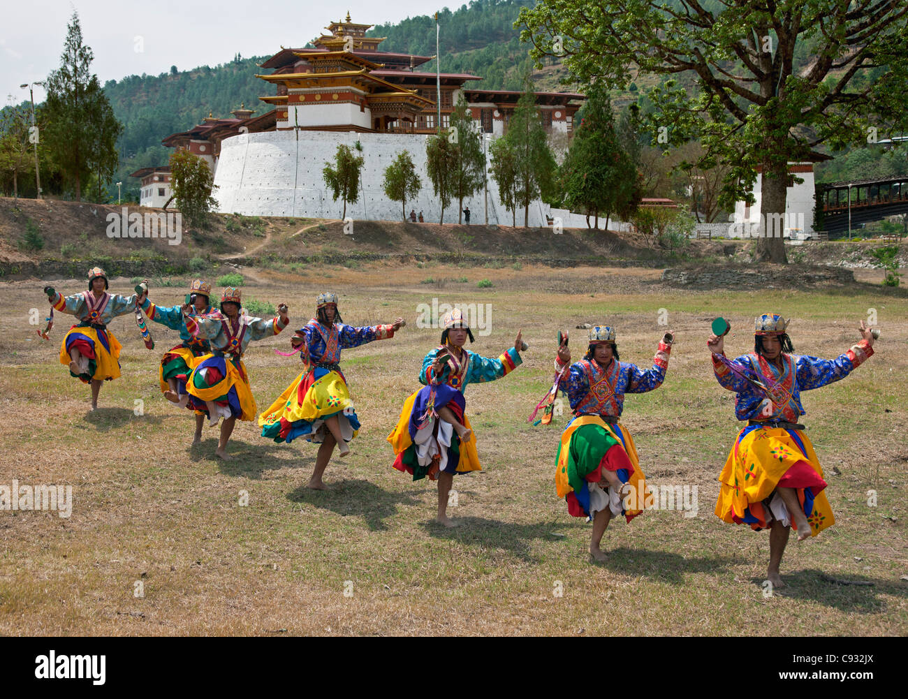 Dancers perform Pa-Cham, the Dance of the Heroes, outside Punakha Dzong. - Stock Image