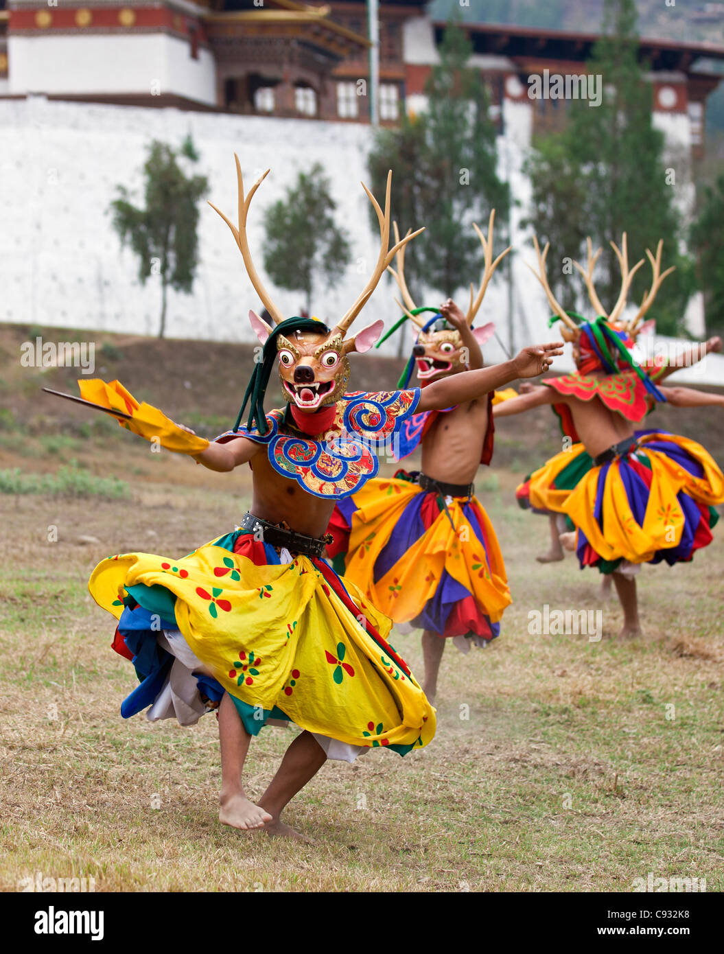 Dancers perform Shazam Tam, the Dance of the Four Stags outside Punakha Dzong. - Stock Image