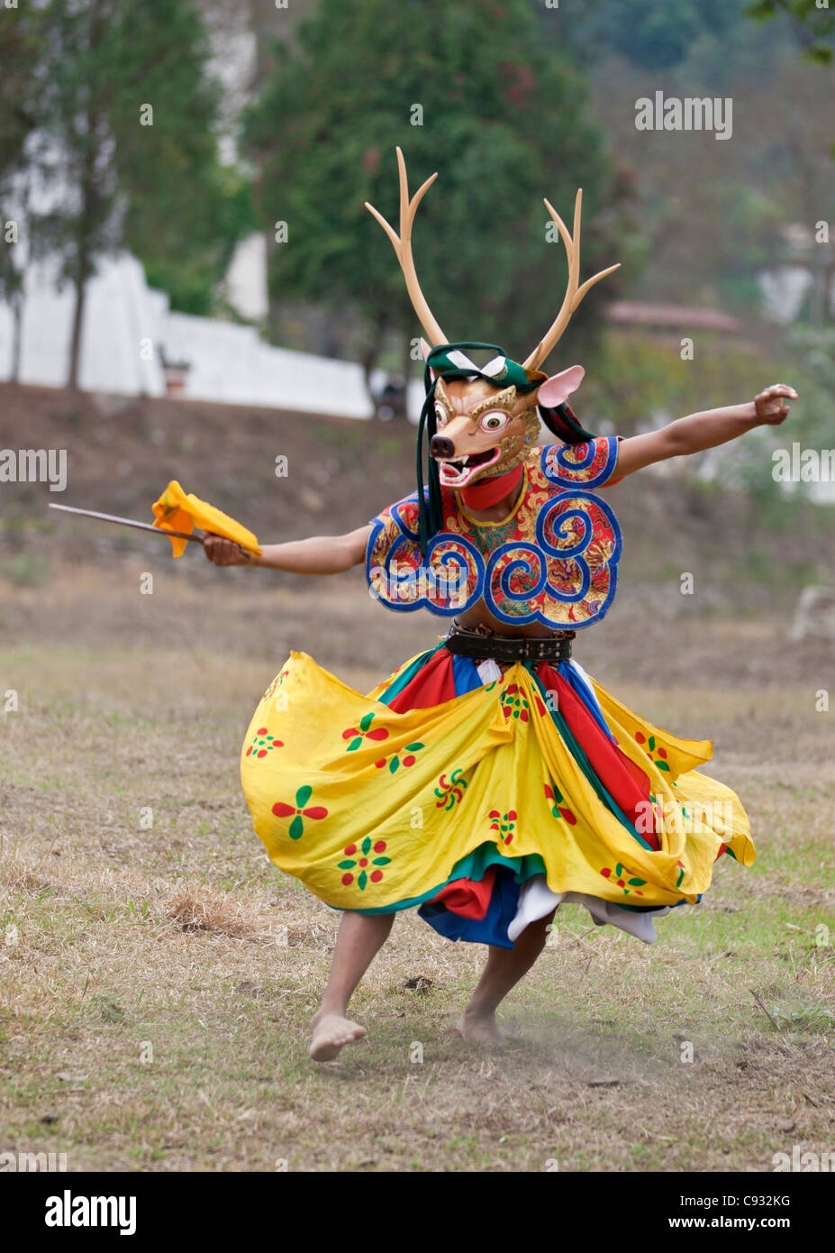 A dancer performs Shazam Tam, the Dance of the Four Stags outside Punakha Dzong. - Stock Image