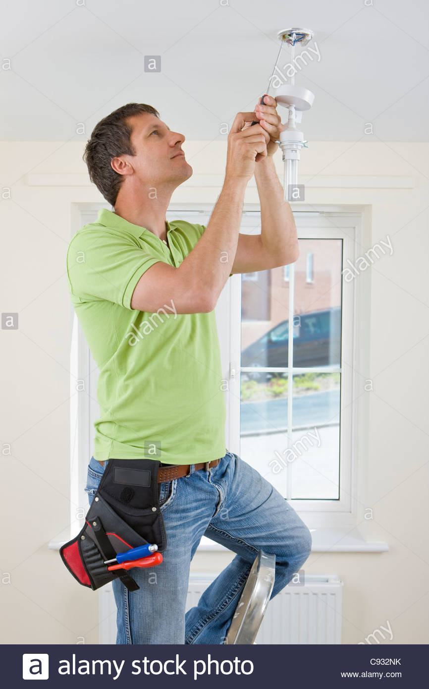 Electrician installing overhead light with compact fluorescent light bulb - Stock Image