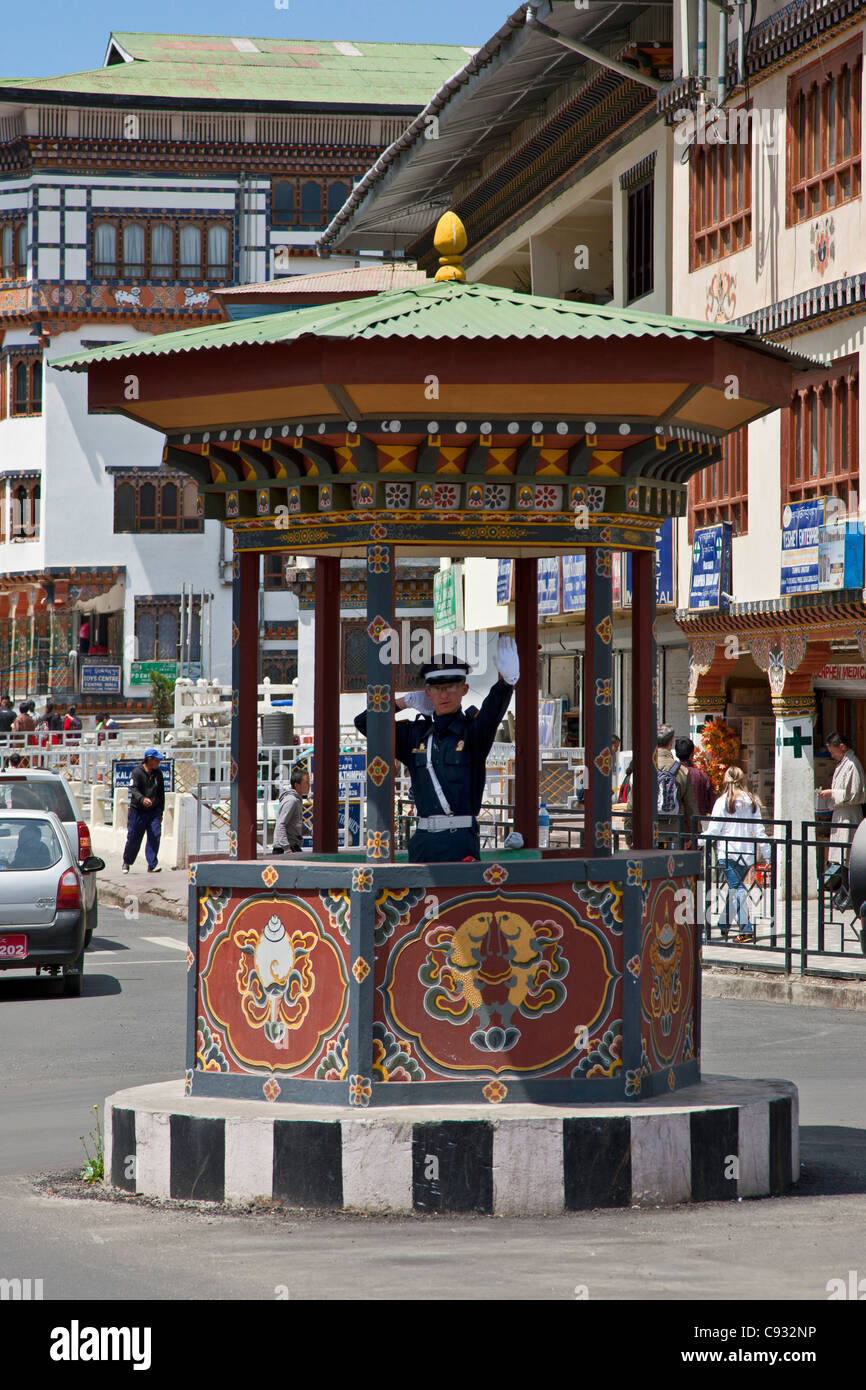 A white-gloved traffic policeman directs traffic at a busy crossroads in the centre of Thimphu. - Stock Image