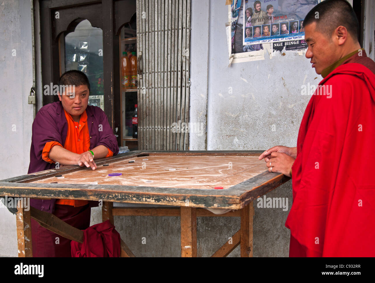 Two monks play Carrom on a shop veranda on the outskirts of Thimphu. - Stock Image