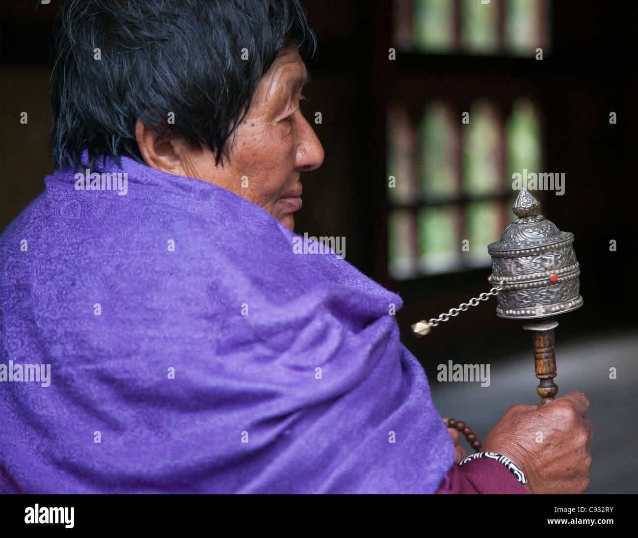 A woman spins her hand-held prayer wheel at the Changangkha Temple on the outskirts of Thimphu. - Stock Image