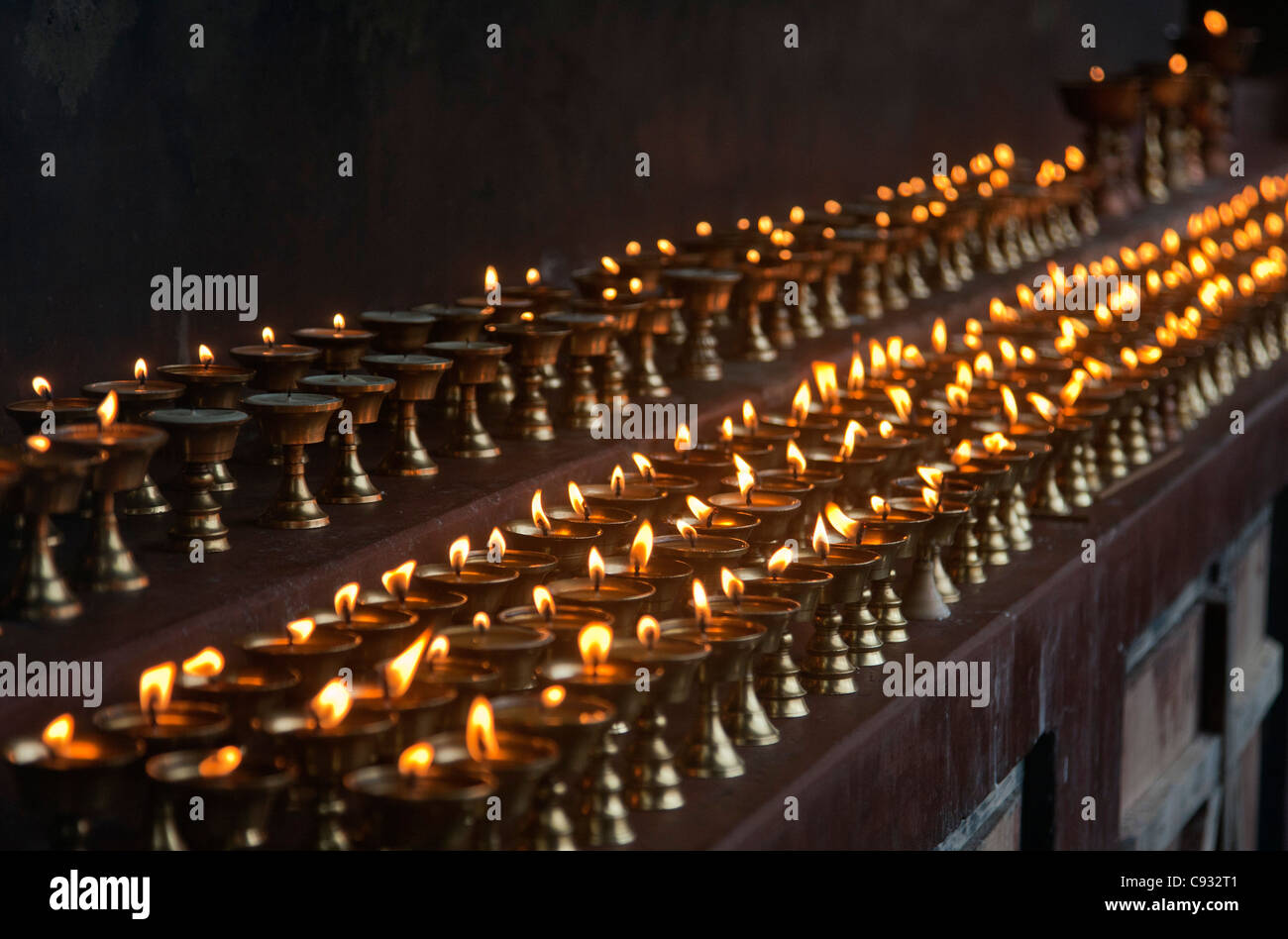 A long line of butter lamps burning at the Changangkha Temple, a fine 15th century temple, on the outskirts of Thimphu. - Stock Image