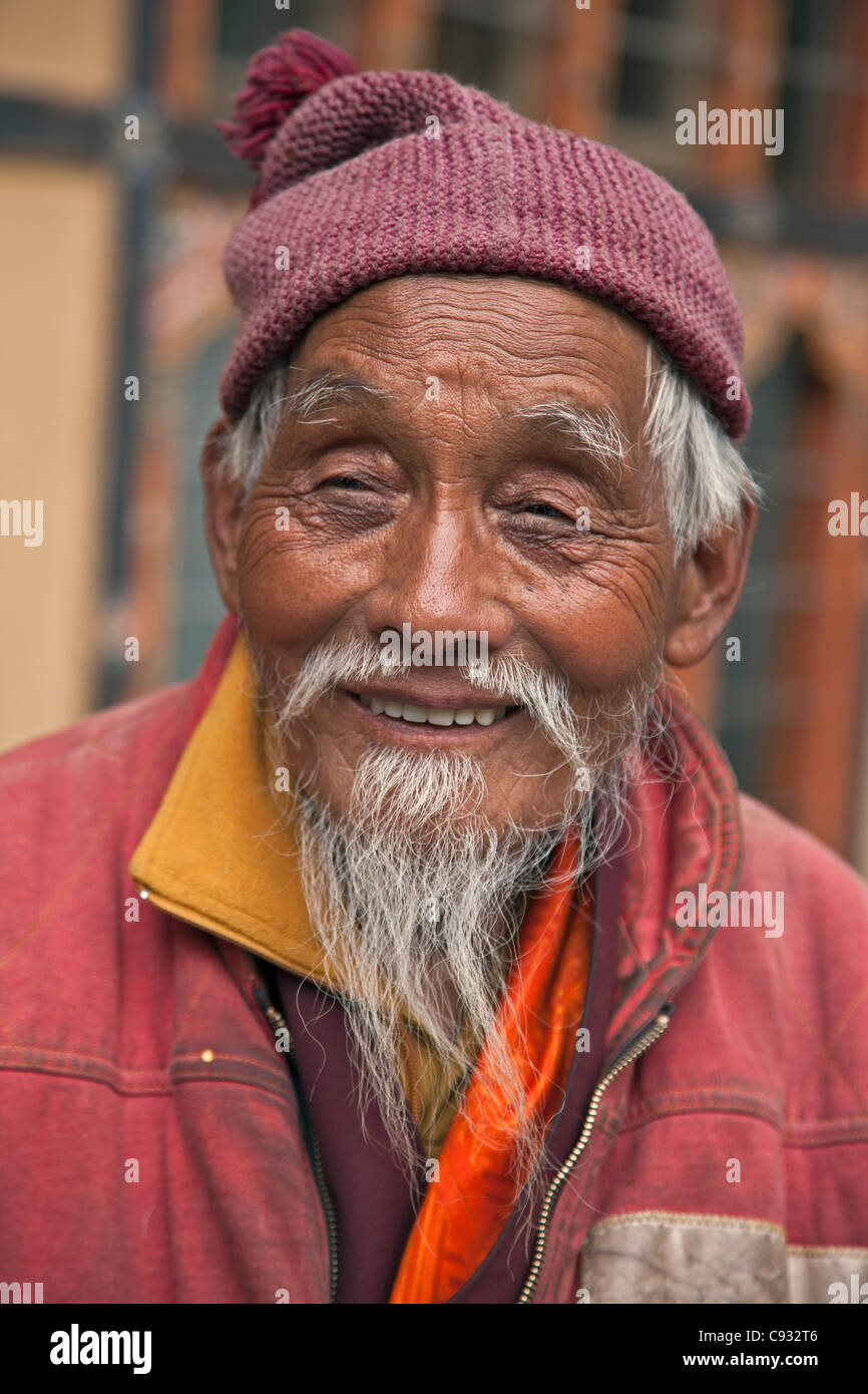 A jovial old monk outside the Changangkha Temple, a fine 15th century temple, on the outskirts of Thimphu. - Stock Image