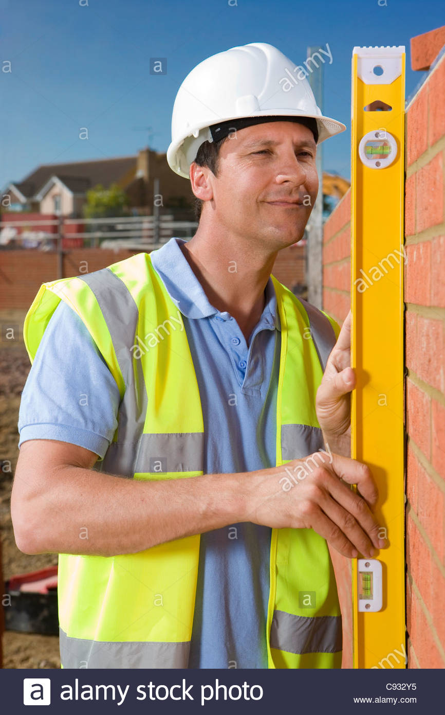 Bricklayer holding level tool against brick wall - Stock Image