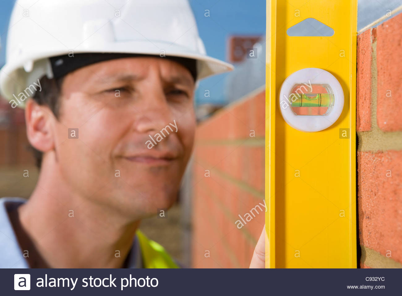 Close up of bricklayer holding level tool against brick wall - Stock Image