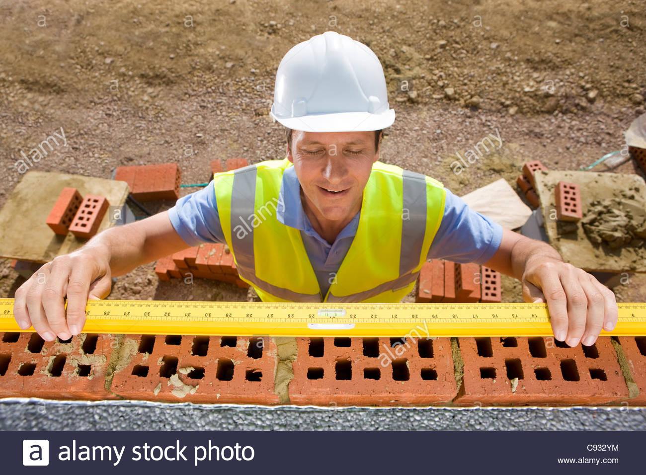 Bricklayer holding carpenter rule along bricks on wall - Stock Image